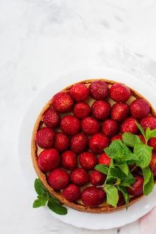 Cheesecake met verse aardbeien en munt op witte plaat op grijze betonnen ondergrond. bovenaanzicht