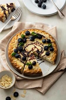 Cheesecake-plak met bosbessen en amandelvlokken met bestek op een licht bovenaanzicht als achtergrond
