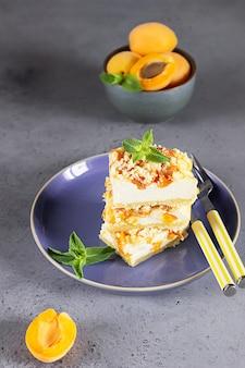 Cheesecake repen met abrikoos en streusel op blauwe keramische plaat versierd met munt