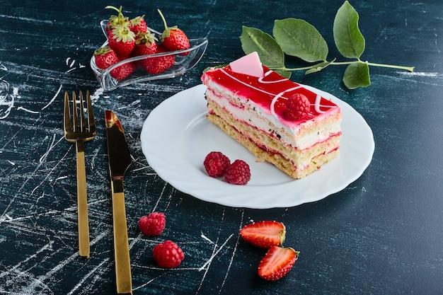 Cheesecake slice met frambozensiroop geïsoleerd op blauwe achtergrond in een witte plaat.