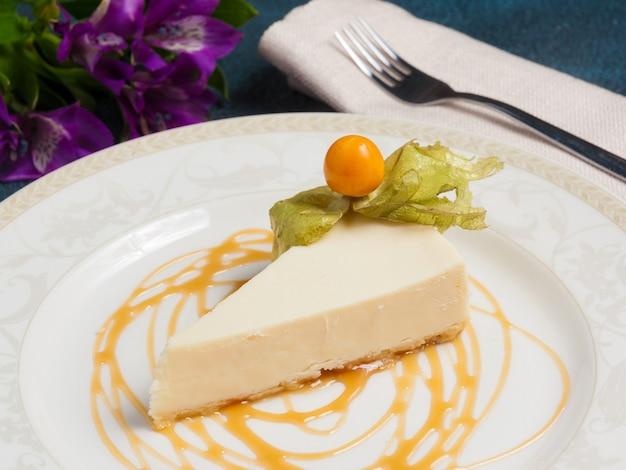 Cheesecake versierd met physalis, karamel en bloemen