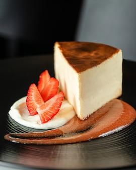 Cheesecake versierd met verse aardbeien en jam op zwarte plaat