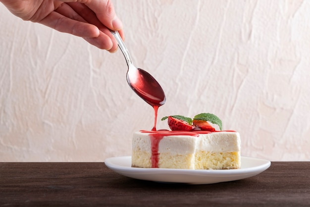 Cheesecake wordt overgoten met bessensiroop. delicaat dessert gegarneerd met verse aardbeien.