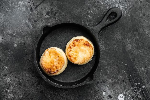 Cheesecakes hartige kwarkpannenkoekjes op gietijzeren koekenpan op gietijzeren koekenpan, bovenaanzicht plat, op zwarte donkere stenen tafel
