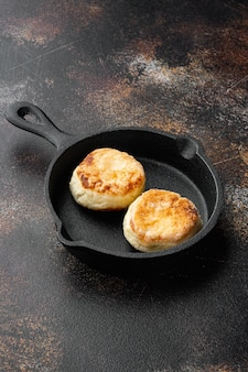 Cheesecakes hartige kwarkpannenkoekjes op gietijzeren koekenpan op gietijzeren koekenpan, op oude donkere rustieke tafelachtergrond