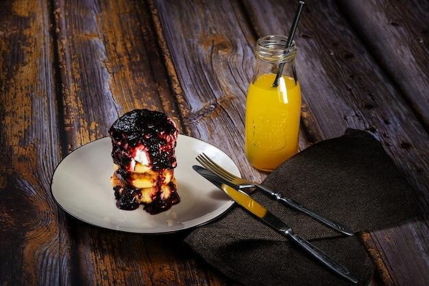 Cheesecakes met bosbessenjam en zure room op een bord met sinaasappelsap in een fles.