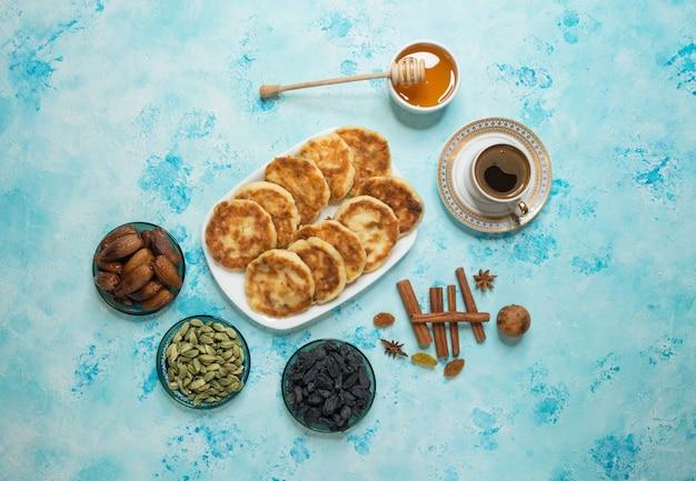 Cheesecakes met honing, dadels en koffie op de tafel.