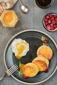 Cheesecakes met verse room en honing, bovenaanzicht.