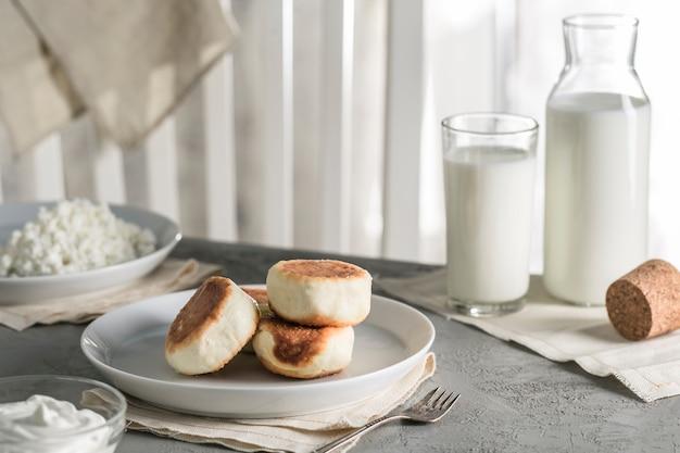 Cheesecakes van kwark op een bord met zure room en een glas melk.