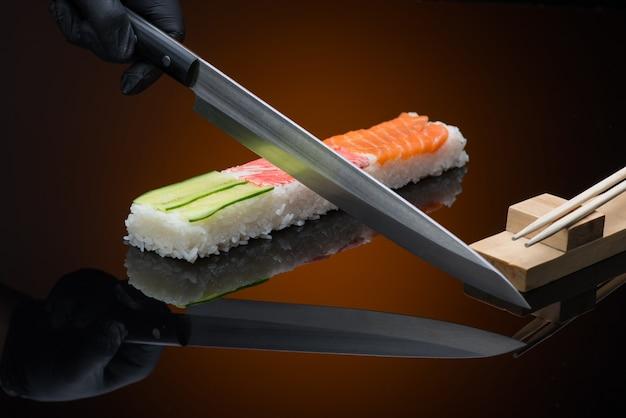 Chef bereidt sushi, snijdt met een mes. sushi op rode achtergrond met reflectie