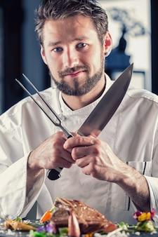 Chef. chef-kok grappig. chef-kok met mes en vork gekruiste armen. professionele chef-kok in een restaurant of hotel bereidt of snijdt t-bone steak. chef-kok die biefstuk bereidt. koken voor hun werk aan catering