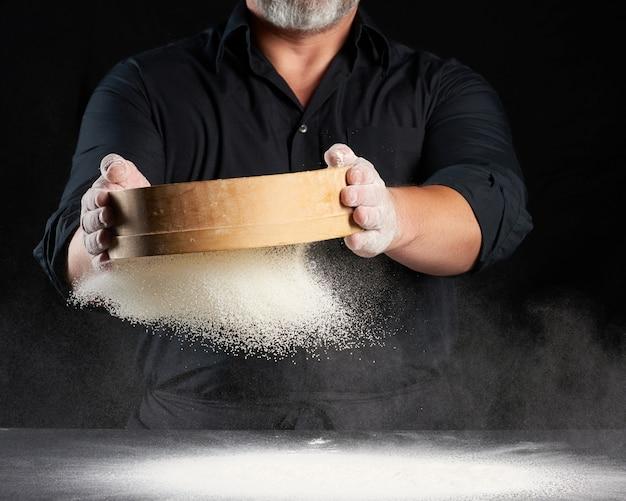 Chef een man in een zwart uniform houdt een ronde houten zeef in zijn handen en zeeft wit tarwemeel op een zwarte achtergrond, de deeltjes vliegen in verschillende richtingen, stoffige ruimte