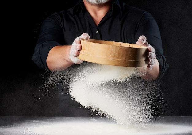 Chef een man in een zwart uniform houdt een ronde houten zeef in zijn handen en zeeft wit tarwemeel op een zwarte achtergrond, de deeltjes vliegen in verschillende richtingen