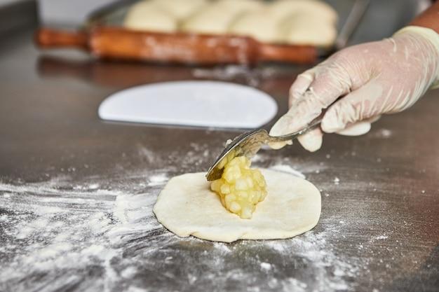 Chef handen bereidt appeltaarten in de keuken van het restaurant. het proces van het maken van zoete broodjes. rauw deeg om in de oven te bakken.
