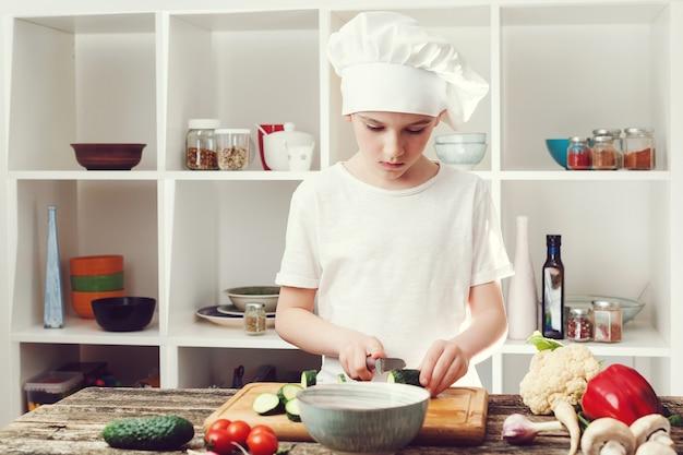 Chef jongen snijden groenten voor salade. kleine chef-kok die kookt in de thuiskeuken. jongen die chef-kokhoed draagt.