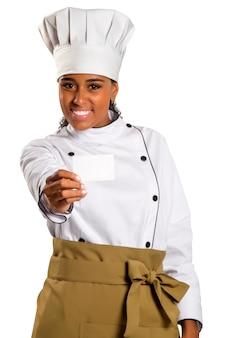 Chef-kok, bakker of kokvrouw die lege tekenkaart tonen die eenvormige chef-koks en hoed dragen. blanco kaart voor menu, cadeaubon, aanbieding enz. mooie afrikaanse / zwarte vrouw geïsoleerd op een witte ruimte