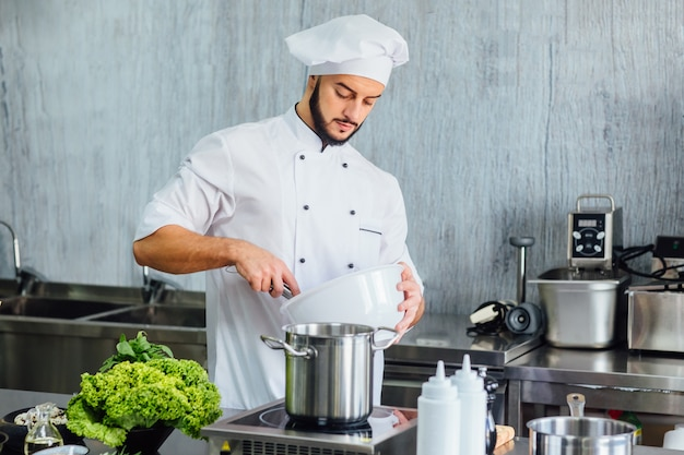 Chef-kok bereiden van voedsel in de keuken van het moderne restaurant