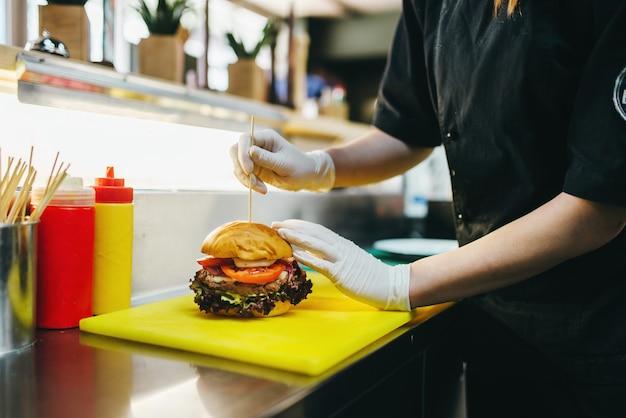 Chef-kok bereidt hamburger, fastfood koken. hamburger bereidingsproces, fastfood