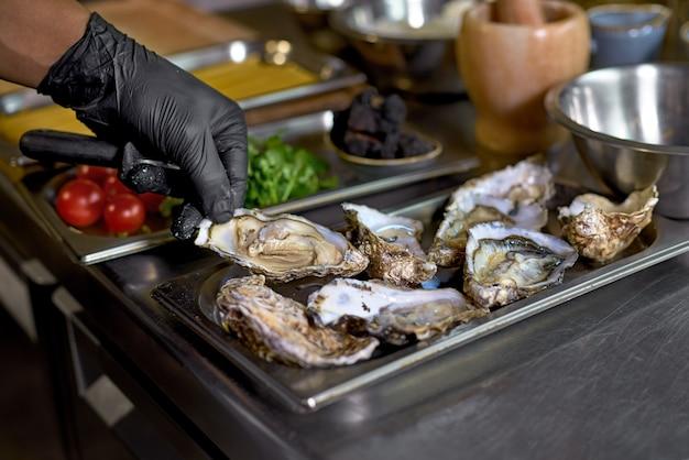 Chef-kok bereidt oesters voor een gerecht op een tafel in de keuken,
