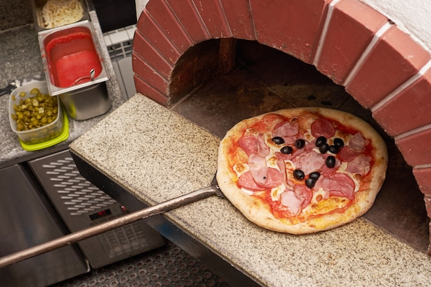 Chef-kok bereidt pizza in traditionele bakstenen oven.