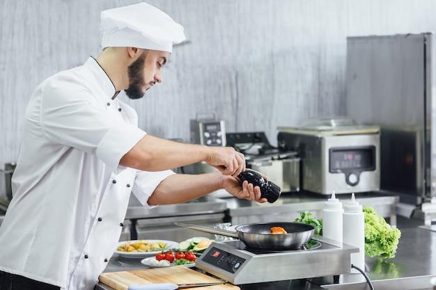 Chef-kok bereidt verse zalmvissen, zout besprenkeld met de ingrediënten. vorst bevriest in de lucht bereiding van het koken van visvoer