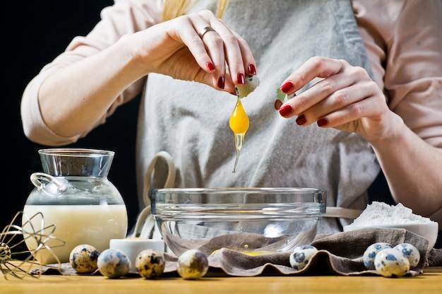 Chef-kok breekt kwarteleitjes in een kom. het concept van het koken van gebak.