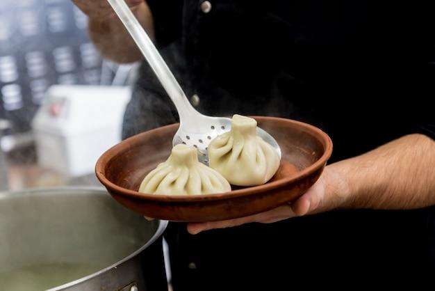 Chef-kok coocking georgische khinkali of japanse wonton.