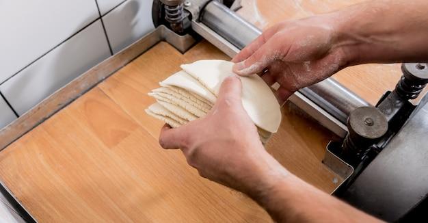 Chef-kok deeg voorbereiden voor gebak, dumplings, italiaanse pasta of japanse wontons.