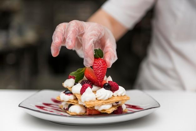 Chef-kok die aardbei op dessert zet