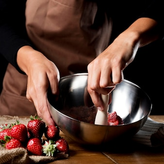 Chef-kok die aardbeien in kom mengen met suiker