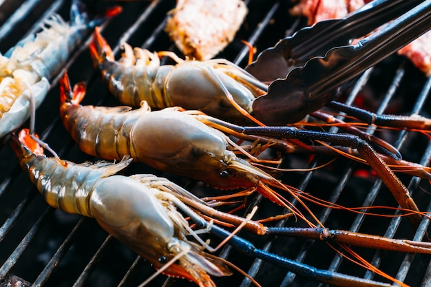 Chef-kok die barbecue met geroosterde garnalen, varkensvlees en kip koken terwijl de zomervakantie