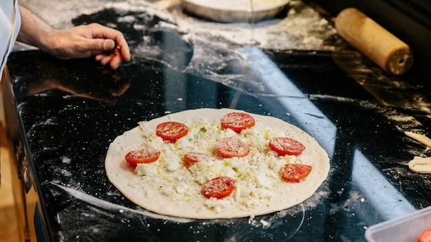 Chef-kok die caprese bianca pizza maakt door olijfolie op deeg toe te voegen.