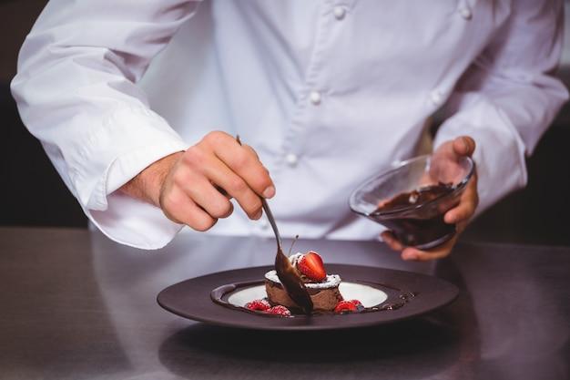 Chef-kok die chocoladesaus op een dessert zet
