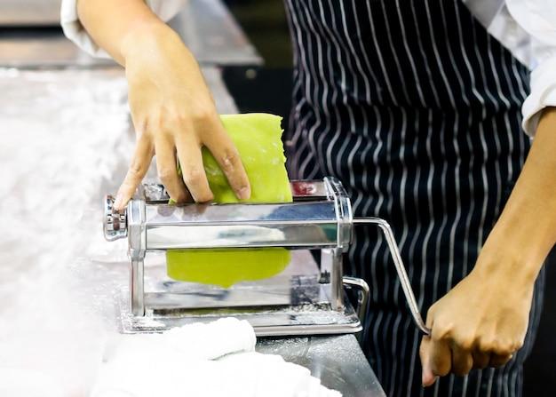 Chef-kok die deeg voor gebakje, verse deegwaren en deegwarenmachine op keuken maakt