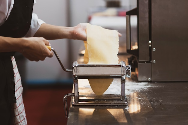 Chef-kok die deegwaren met een machine, eigengemaakte verse deegwaren maakt