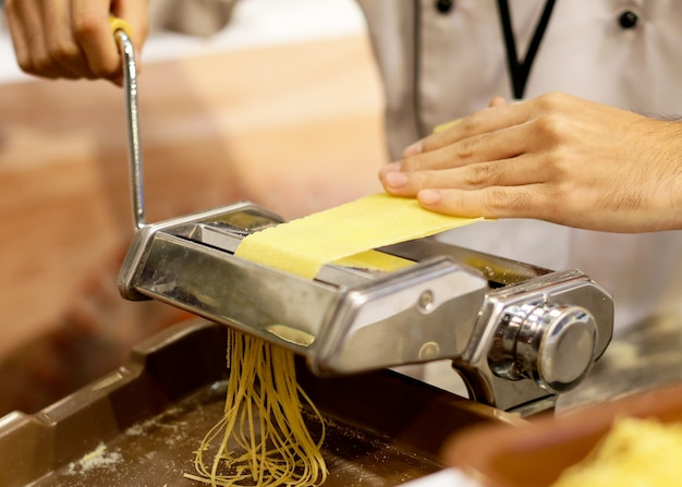 Chef-kok die deegwaren met een machine maakt, naar huis gemaakte verse deegwaren