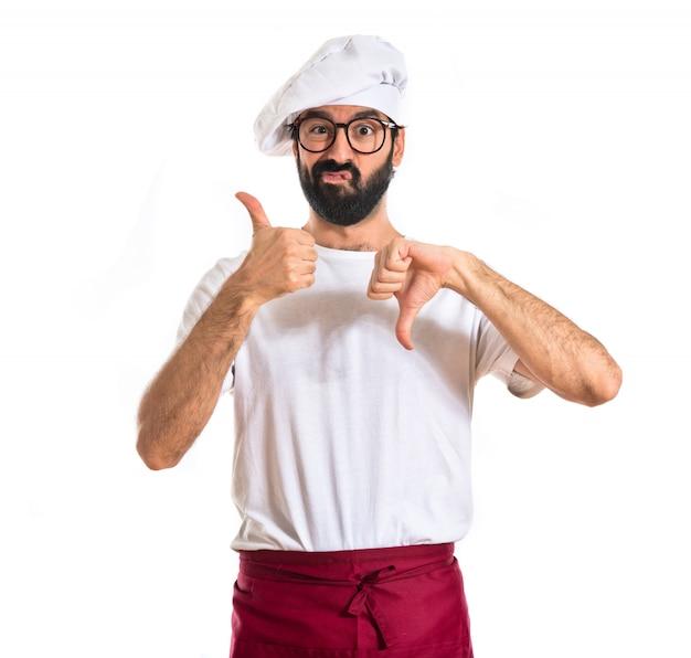 Chef-kok die een goed-slecht teken op een witte achtergrond maakt