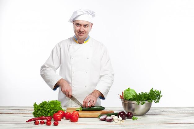 Chef-kok die een groene komkommer in zijn keuken snijdt