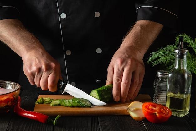 Chef-kok die een groene komkommer snijdt in de keuken in het restaurant