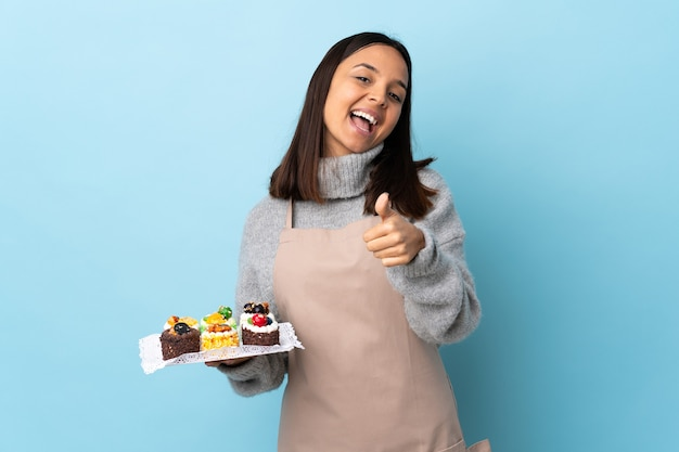 Chef-kok die een grote cake over geïsoleerde blauwe achtergrond met omhoog duimen houdt omdat er iets goeds is gebeurd.