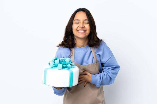 Chef-kok die een grote cake over geïsoleerde witte achtergrond houdt die veel glimlachen