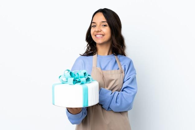 Chef-kok die een grote cake over het geïsoleerde witte muur houden lachen