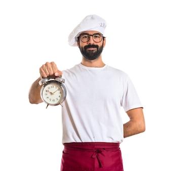 Chef-kok die een klok over witte achtergrond houdt
