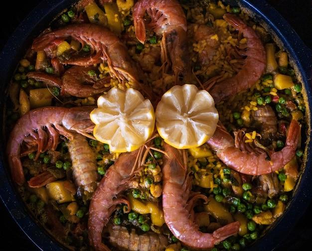 Chef-kok die een paella kookt die borrelt met garnalen, citroen en diverse zeevruchten. het voorbereiden van typische heerlijke spaanse voedseltapa. lekker gerecht uit spanje