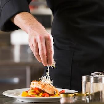 Chef-kok die een schotel van gezond voedsel voorbereidt