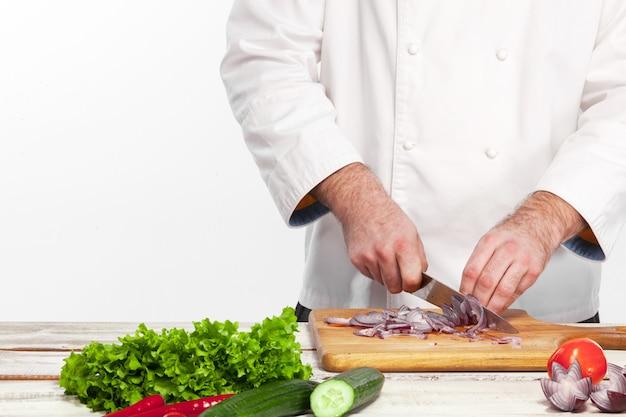 Chef-kok die een ui op zijn keuken snijdt