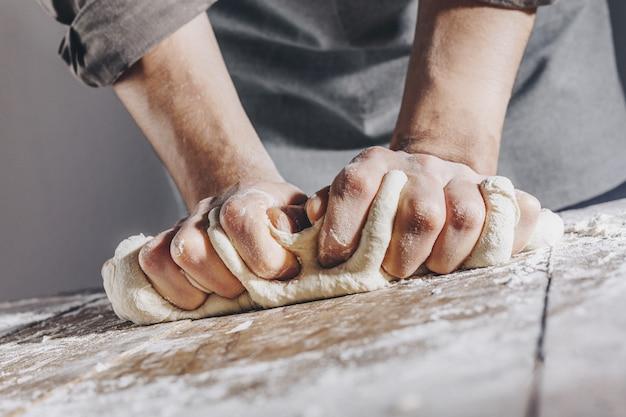 Chef-kok die en vers deeg maakt kneden