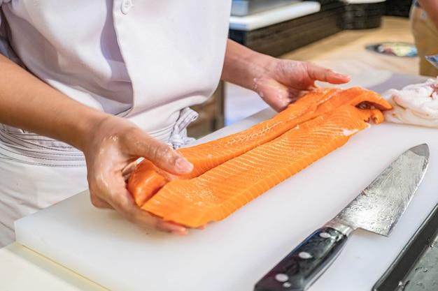 Chef-kok die en verse zalm in japans restaurant voorbereidt snijdt
