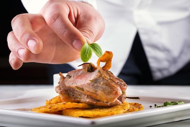Chef-kok die extra kruid bovenop geroosterd vlees met aardappelpannekoeken zet.