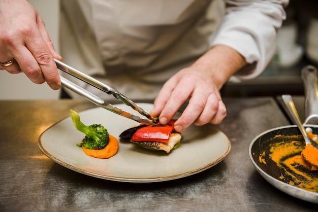 Chef-kok die gastronomisch schotel vooraanzicht voorbereidt